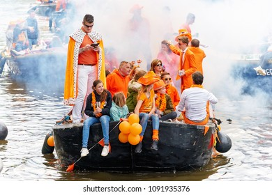 AMSTERDAM - APRIL 27, 2018: People in orange costumes having fun in the boat in Amsterdam during the Kingsday 2018 celebrations.