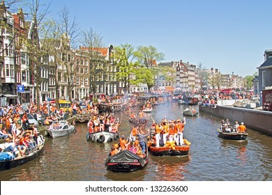 AMSTERDAM - APRIL 30: Amsterdam canals full of boats and people in orange during the celebration of queensday on April 30, 2012 in Amsterdam, The Netherlands