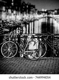Amsterdam bicycles on bridge and night lights reflected in channel, monochrome