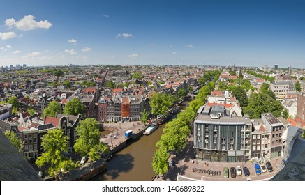 Amsterdam blue sky view over city rooftops, pretty tree lined Prinsengracht canal and Anne Frank House (right).