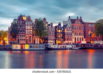 Amsterdam canal Amstel with typical dutch houses and boats during twilight blue hour, Holland, Netherlands. Used toning