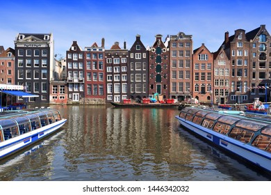 Amsterdam canal architecture - Damrak canal waterfront in De Wallen district.