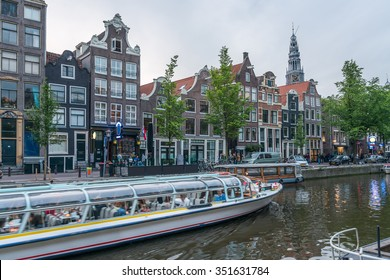 Amsterdam Canal Cruise Rederij Lovers Plas Moving glass-topped Tour Culinary Dinner Boat full of Tourist people in Canal of Amsterdam under Dramatic Golden Sky Sunset in Summer Evening, Netherlands