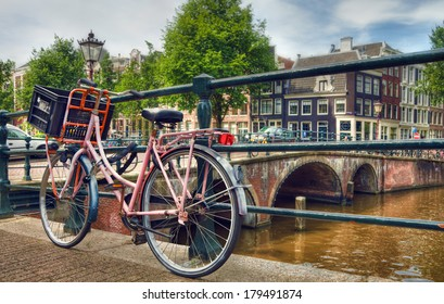 Amsterdam canal scene with a pink bicycle and brick bridges.