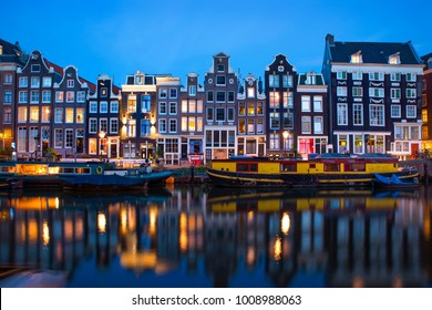 Amsterdam canal Singel with typical dutch houses and houseboats at evening with beautiful water reflections, Holland, Netherlands.
