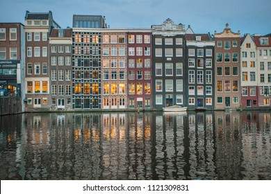 Amsterdam canal Singel with typical dutch houses illuminated in the evening. Illuminated buildings reflection in the Amsterdam canal. Holland, Netherlands. 101 May 2018