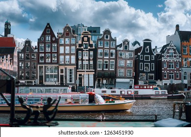 Amsterdam canal Singel with typical dutch houses and houseboats with beautiful cloudscape in background, Holland, Netherlands