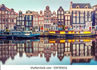 Amsterdam Kanal Singel mit typischen Häusern und Hausbooten während der Morgenblauen Stunde, Holland, Niederlande. Verwendete Tönung.