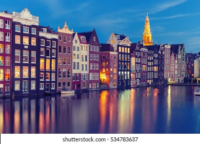 Amsterdam canal with typical houses and Oude Kerk church during twilight blue hour, Holland, Netherlands. Used toning