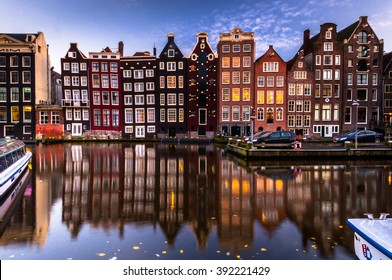 Amsterdam canal view at night. Reflection of houses at water.