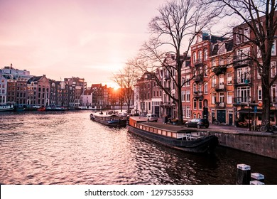 Amsterdam canals house architecture with boats during sunset, Amsterdam Holland Netherlands winter aerial view