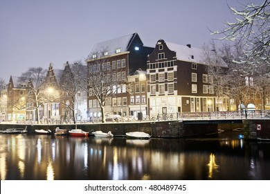 Amsterdam canals and typical houses on a snowy winter night