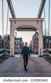 Amsterdam city canal aerial view,Skinny Bridge (Dutch: Magere Brug) over the Amstel river in Amstel, young woman at the bridge
