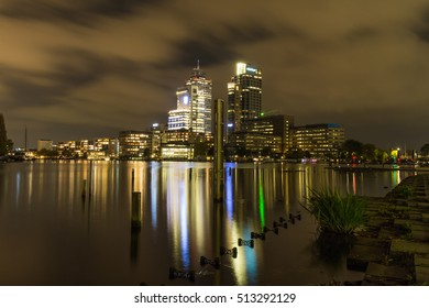 The Amsterdam city center by night, featuring a modest skyline composed of the Rembrandt, Mondriaan and Breitner towers on the bank of the Amstel river.