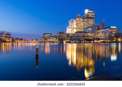 Amsterdam city night skyline with Rembrandt, Breitner and Mondriaan Tower near the Amstel river at sun set during the blue hour with colorful light reflections in the water.
