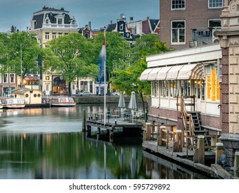 Amsterdam City Panorama at night, historic apartment houses with water reflections, boats for canal tour cruise on Amstel river, Pathe Tuschinski Theater, Cineac casino from Aluminiumbrug, Netherlands
