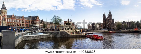Amsterdam City Panorama. StationsPlein, Oosterdok harbor, Walking Tourists and Traditional Dutch architecture near Amsterdam Centraal Railway Station. Amsterdam, The Netherlands - September 26, 2015.