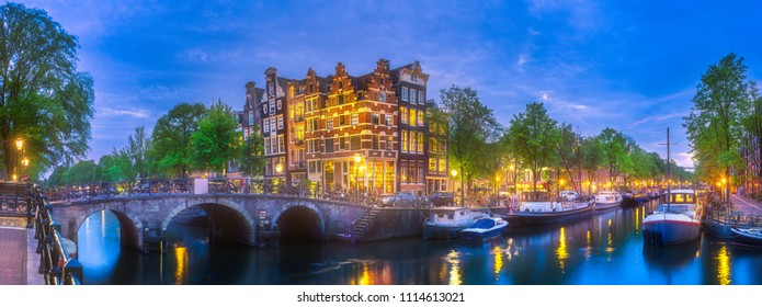Amsterdam city skyline with reflection of houses in river at night, Netherlands.