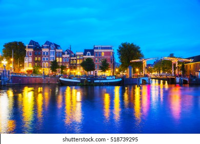 Amsterdam city view with canals and bridges at night