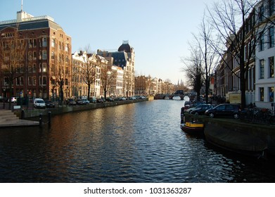 Amsterdam - Classic canal view with houseboats and historic homes lining the canal on a wintry clear day