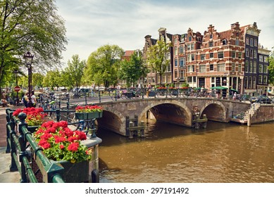 Amsterdam colorful houses, geranium flowers and triple arch bridge at the intersection between Prinsengracht and Brouwersgracht Canals.