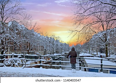 Amsterdam covered with snow  in winter in the Netherlands at sunset