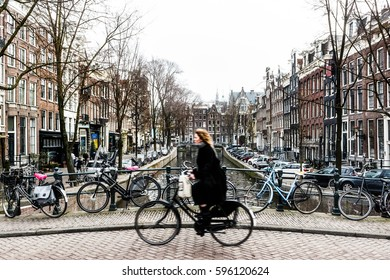 Amsterdam Cyclist traveling over a bridge.