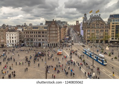 Amsterdam Dam Square view with many tousits and tram on typical dutch cloudy day