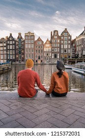 Amsterdam Damrak during sunset, happy couple man and woman on a summer evening at the canals, dutch couple at Waterfront by Dancing house of Amsterdam