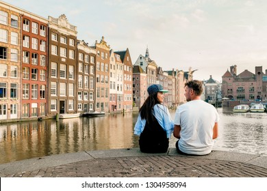 Amsterdam Damrak during sunset, happy couple man and woman on a summer evening at the canals