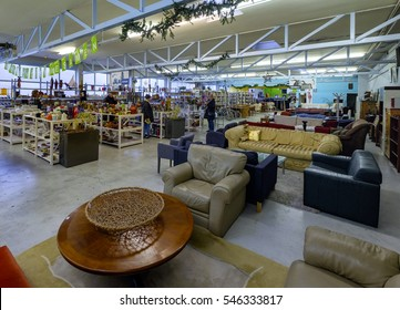 Amsterdam, December 2016: Interior of a second hand shop in an industrial building with a few clients and furniture, pottery and books