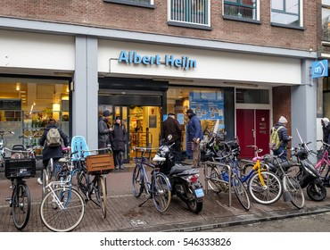 Amsterdam, December 2016: Parked bicycles and customers outside of a branch of Albert Heijn, the biggest Dutch Supermarket chain