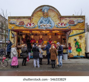 Amsterdam, December 2016: people buying oliebollen, sweet pastry baked in oil, from a stand in the streets