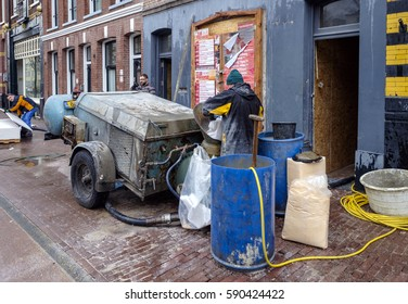 Amsterdam, February 2017. Builder mixing concrete on the pavement outside of a house renovation project in the city