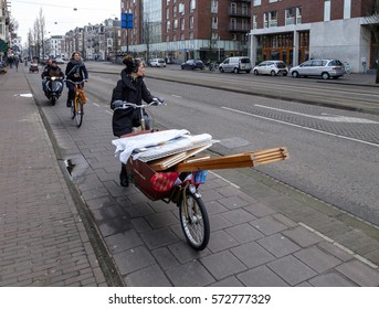 Amsterdam, February 2017. Girl on a delivery bicycle transporting furniture