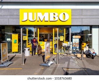 Amsterdam, February 2018. Entrance of a branch of the Dutch Jumbo supermarket chain, with a customer standing near the door.