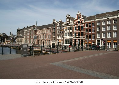 AMSTERDAM, HOLLAND -10 APRIL 2020: Photo taken from a bridge in Amsterdam of beautiful buildings. The city has been abandoned by tourists due to the corona covid 19 virus.