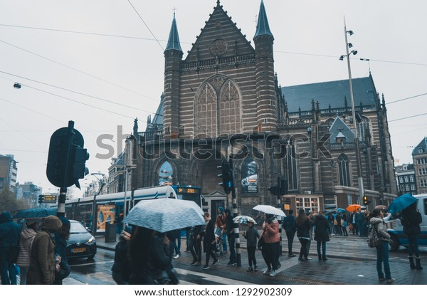 Amsterdam, Holland -29/04/2018:  Rainy day in Amsterdam. Tramway transportation. Street corner, touristic square, iconic house in Amsterdam, Holland. Ancient style.