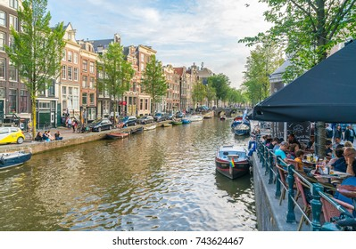 AMSTERDAM, HOLLAND - AUGUST 17, 2017;  People relax late in day sitting alongside canal and in canalside cafes with boast moored on edges backed by traditional architecture that fronts canals.