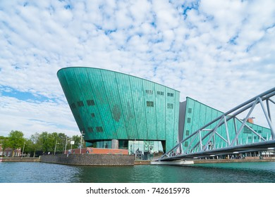 AMSTERDAM, HOLLAND - AUGUST 17; NEMO Large green colored ship shaped building houses science museum with pedestrian bridge crossing canal to its entrance August 17, 2017, Amsterdam, Holland.