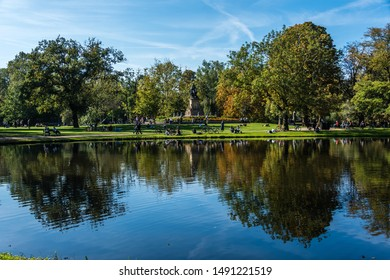 Amsterdam, Holland, August 2019 Reflections at Amsterdam Vondelpark during autumn with trees in beautiful colors reflecting in the water and a statue of Joost van den Vondel