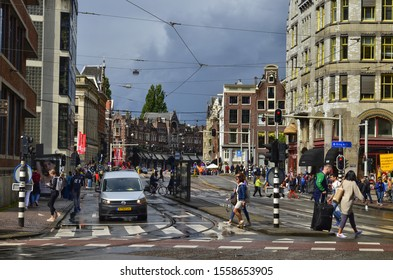 Amsterdam, Holland. August 2019. A road junction in the center: the typical houses, cars, bikes, pedestrians, tram rails coexist. The red asphalt reserved for bikes stands out.