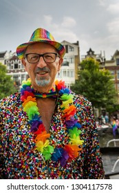Amsterdam, Holland - August 4 2018 : Male spectator wearing a rainbow trilby hat, a multi-coloured sequinned suit and a rainbow garland, at the Amsterdam Pride Canal Parade