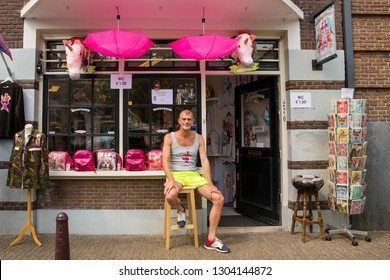 Amsterdam, Holland - August 4 2018 : Shopkeeper sitting on a stool outside his novelty gift shop selling cards, pink umbrellas and bags, during the Amsterdam Pride Canal Parade