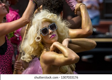 Amsterdam, Holland - August 4 2018 : Close up portrait of a blonde Marilyn Monroe lookalike in gold body paint, sunglasses and a seashell shaped bikini, posing at the Amsterdam Pride Canal Parade