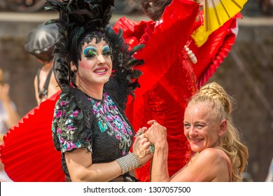 Amsterdam, Holland - August 4 2018 : Liza Minelli lookalike drag queen dressed in black feather boas with sparkly dramatic make up, with an old blonde female at the Amsterdam Pride Canal Parade