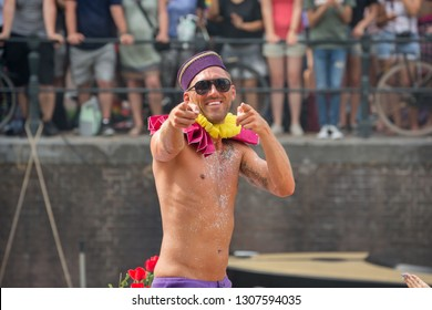 Amsterdam, Holland - August 4 2018 : Male participant with glittery chest dressed in a bellboy hat and yellow and pink ruffs pointing to the camera and smiling at the Amsterdam Pride Canal Parade