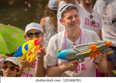 Amsterdam, Holland - August 4 2018 : Man and boy shooting from large colourful water blaster guns into the crowd, from aboard a float at the famous Amsterdam Canal Parade