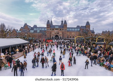 Amsterdam, Holland, December 2015: Ice skaters on the ice rink at the Museumplein, with the Rijksmuseum in the background