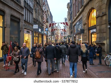 Amsterdam, Holland, December 2016: Crowded high street in December atmosphere, with many people mostly seen on the back, shopping